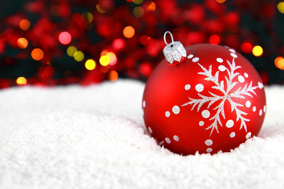 A red Christmas ornament in the snow with lights in the background.