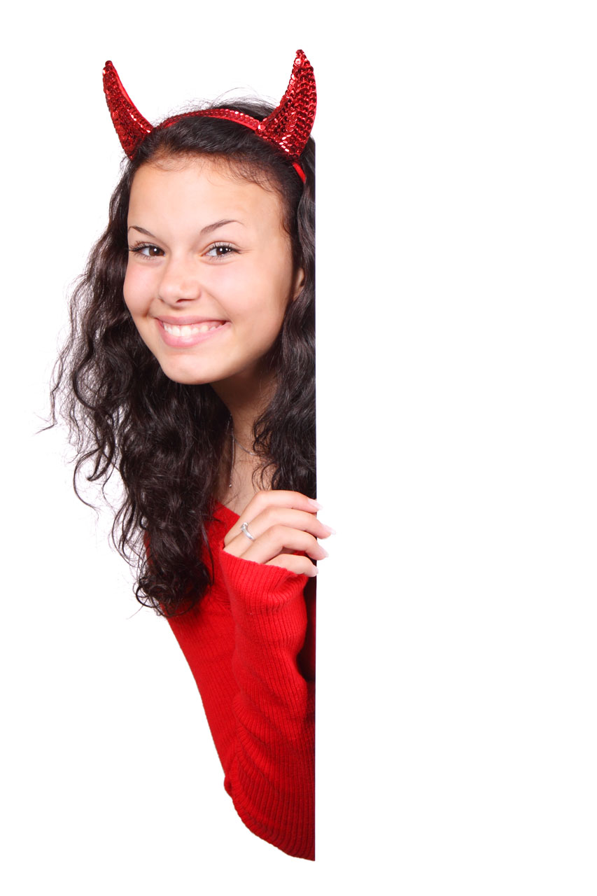 A beautiful girl in a red devil costume isolated on a white background.