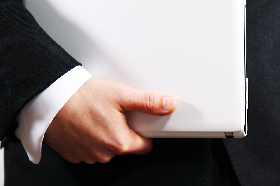 Businessman holding a white laptop : Free Stock Photo