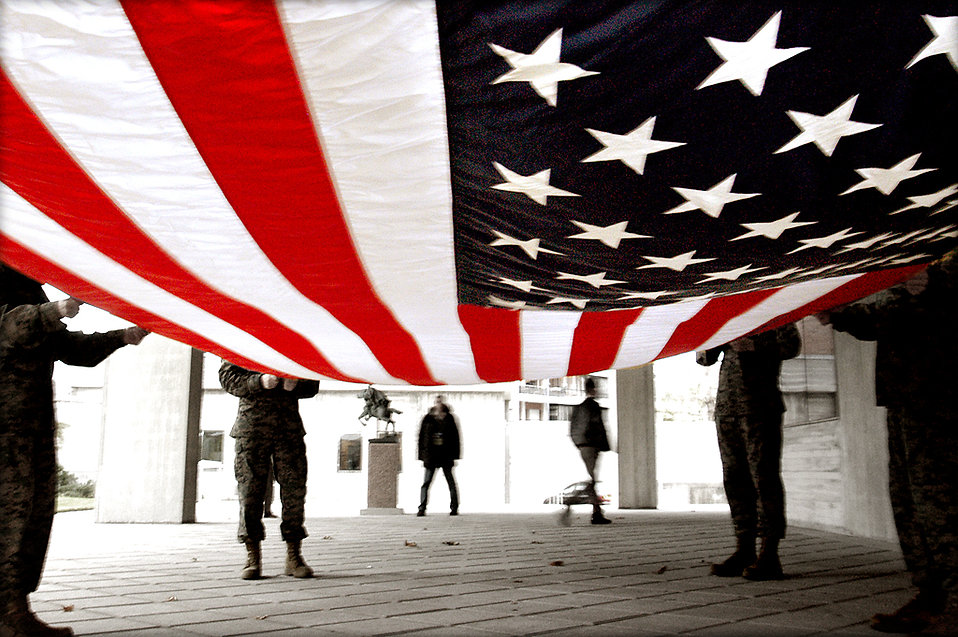 Soldiers preparing to fold an American flag.