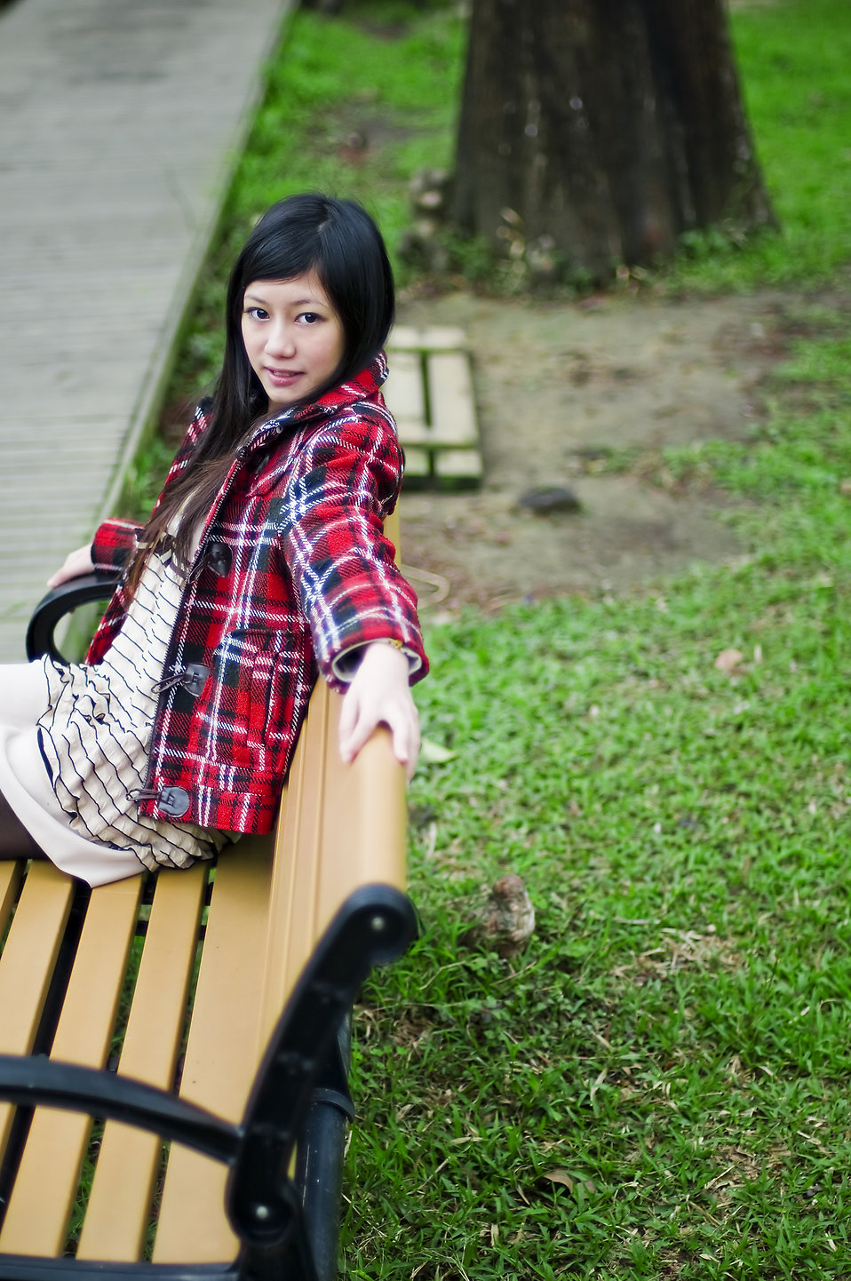 A beautiful Chinese girl posing on a bench : Free Stock Photo