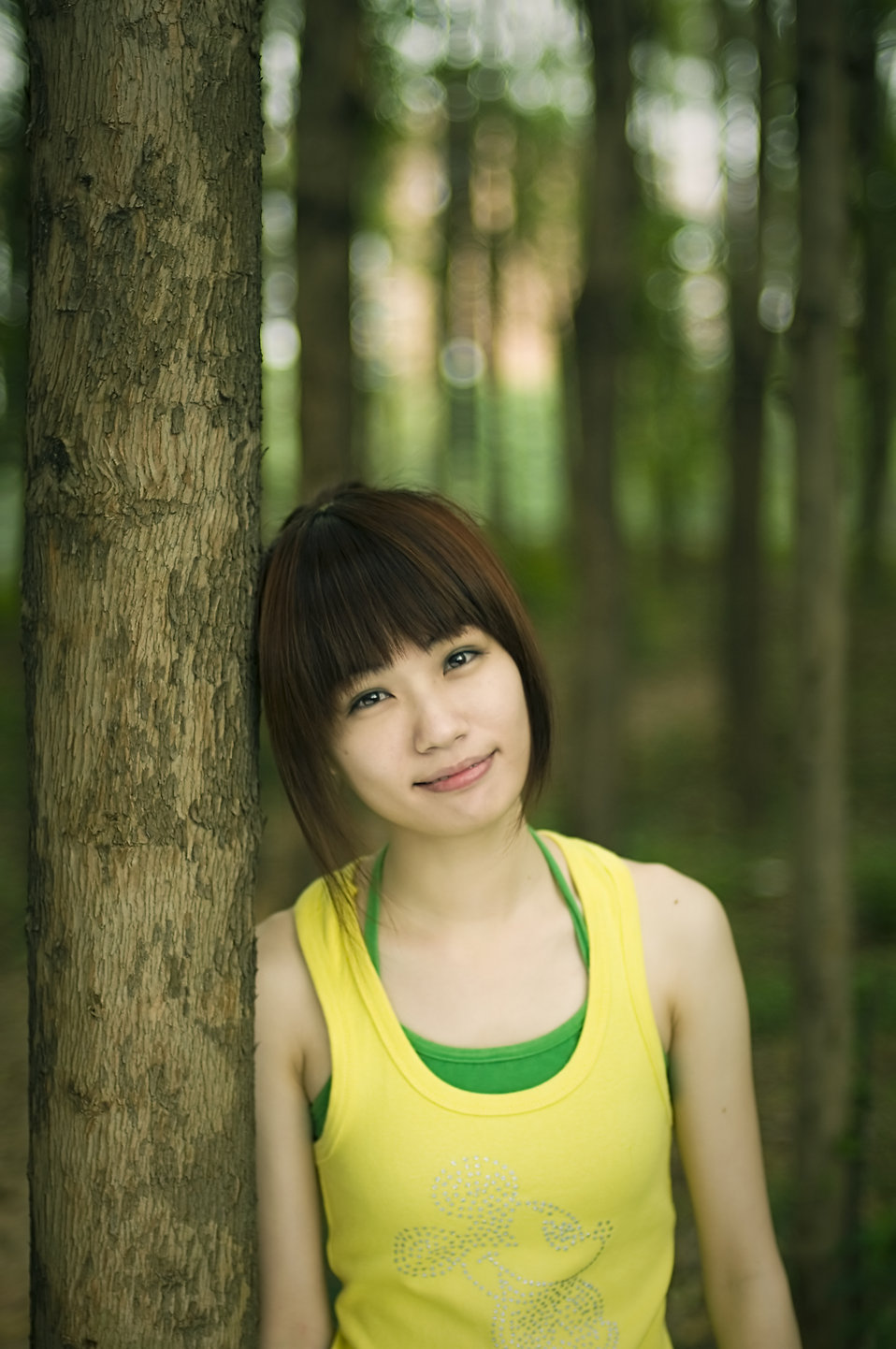 A beautiful Chinese girl posing against a tree : Free Stock Photo
