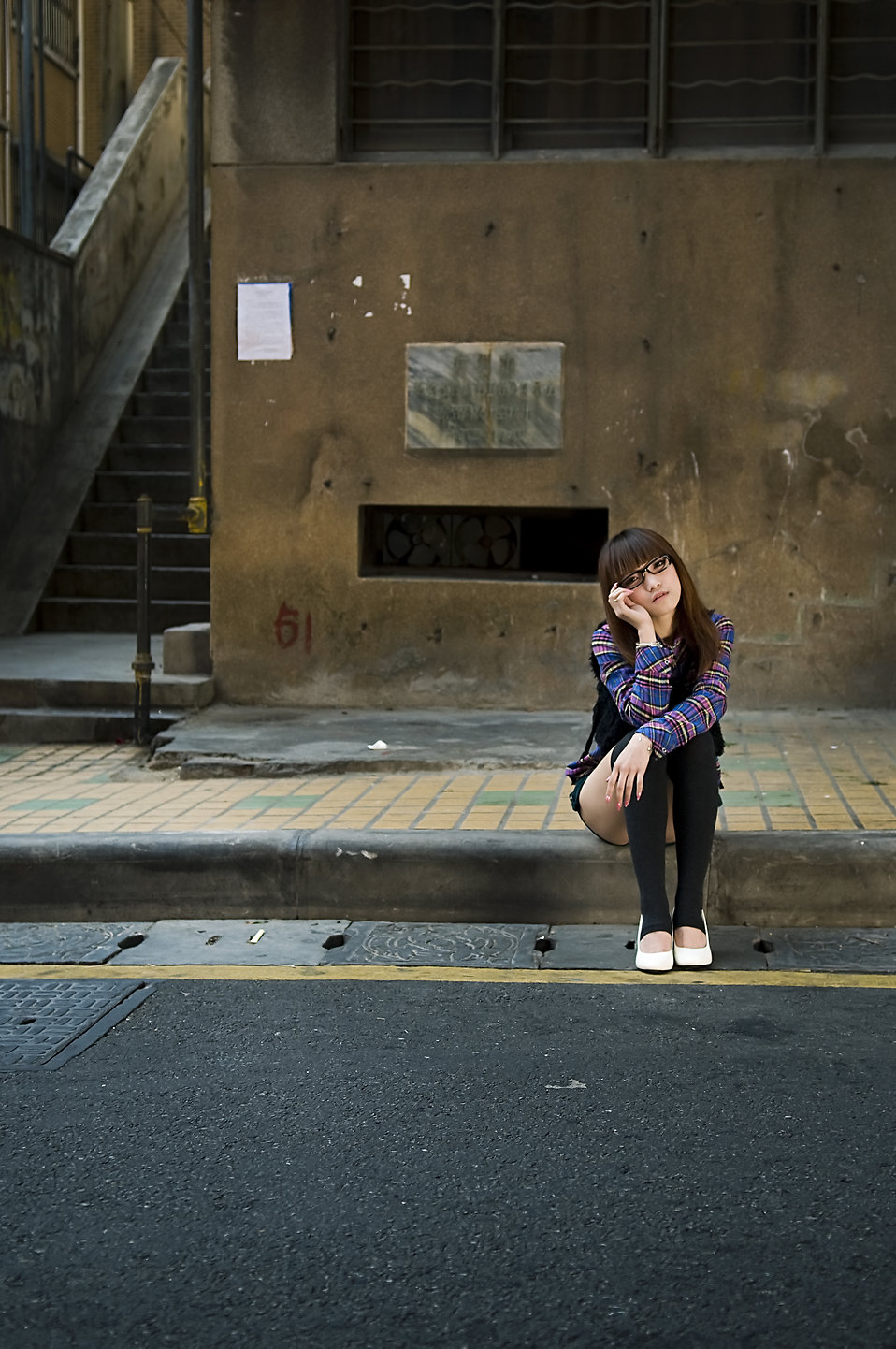 A beautiful Chinese girl sitting on a curb : Free Stock Photo