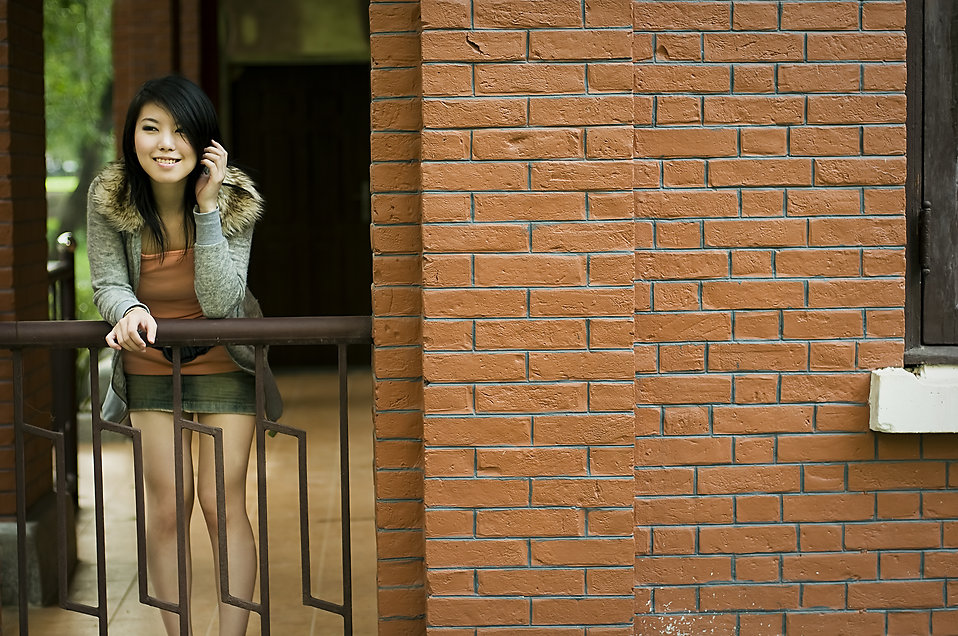A beautiful Chinese girl posing on a railing by a brick wall : Free Stock Photo