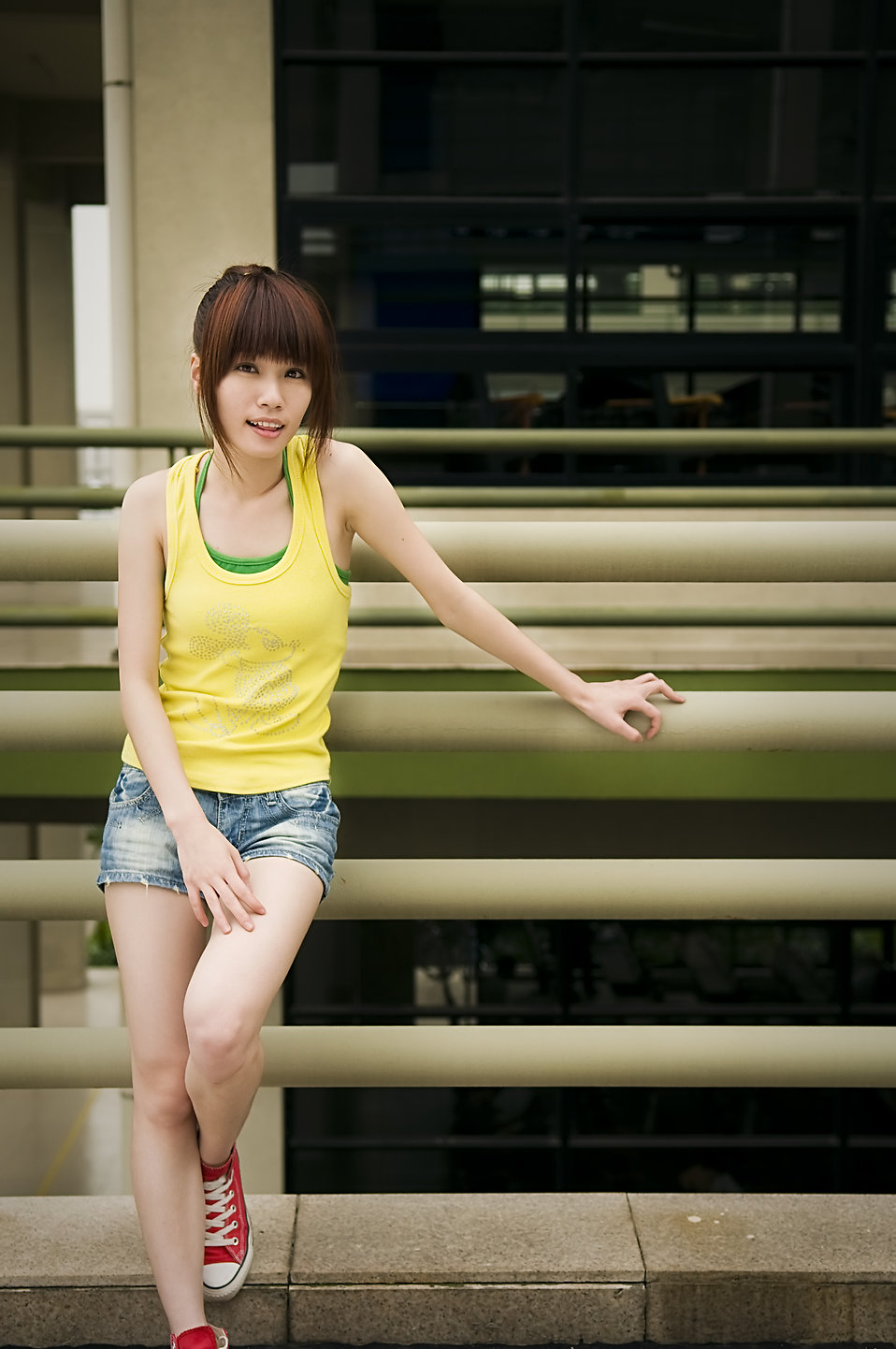 A beautiful Chinese girl posing by against a railing : Free Stock Photo