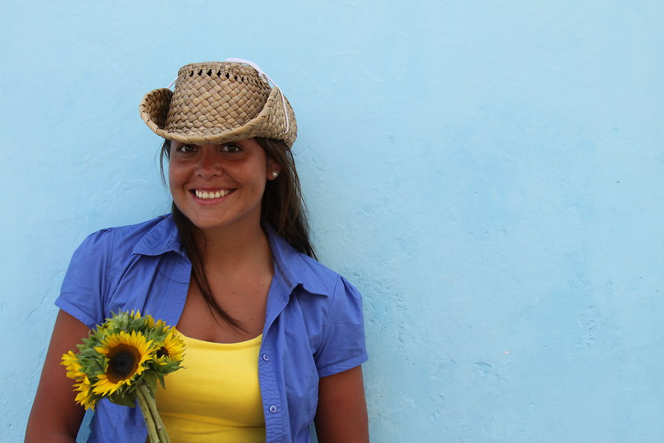 A beautiful girl in a hat holding a sunflower posing against a wall : Free Stock Photo
