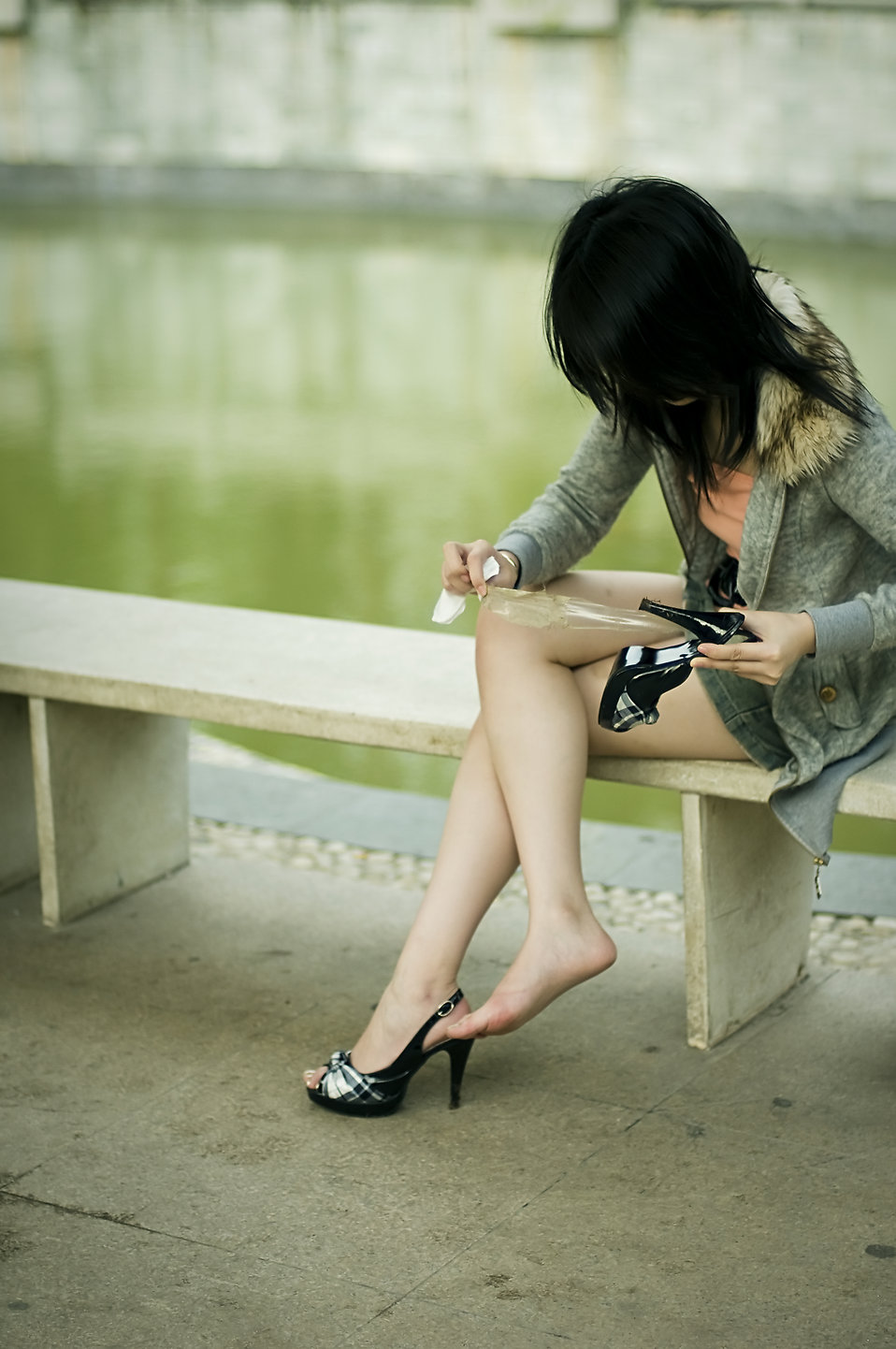 A beautiful Chinese girl sitting on a bench fixing her shoe : Free Stock Photo