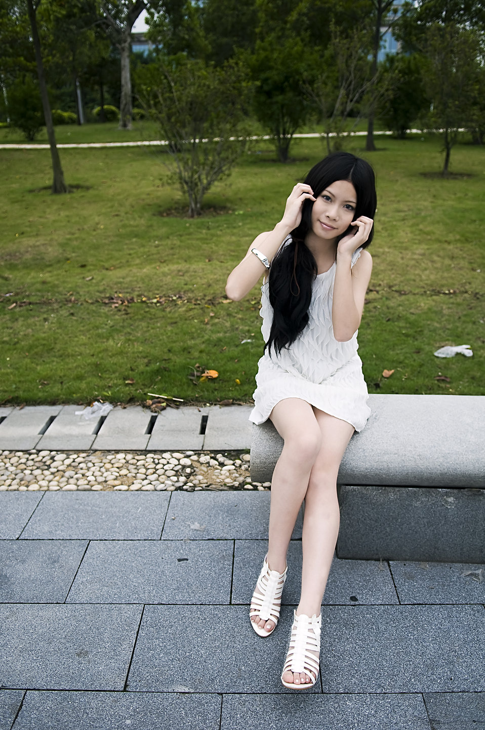 A beautiful Chinese girl posing on a bench outdoors : Free Stock Photo