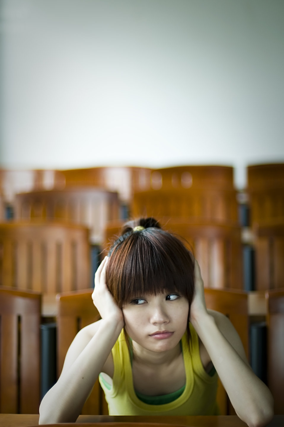 A beautiful Chinese girl sitting tired at a desk : Free Stock Photo