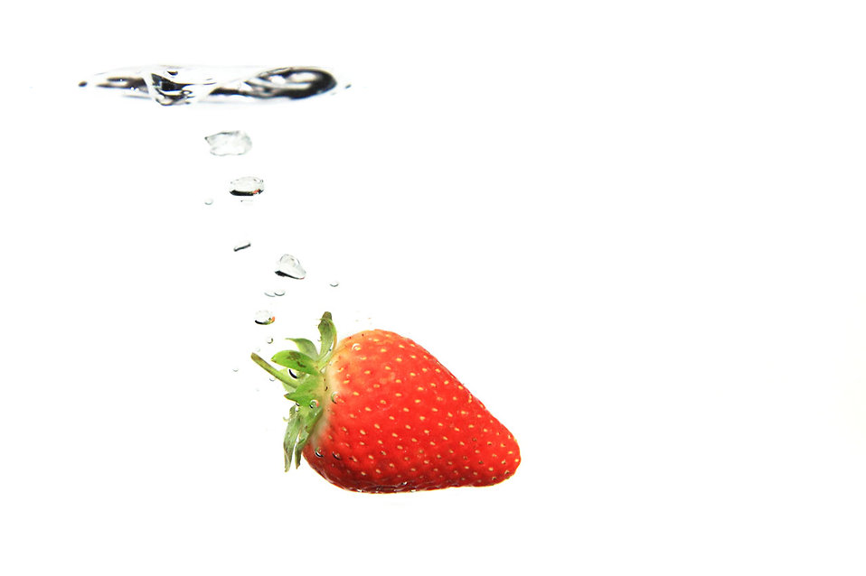 A strawberry splashing in water.
