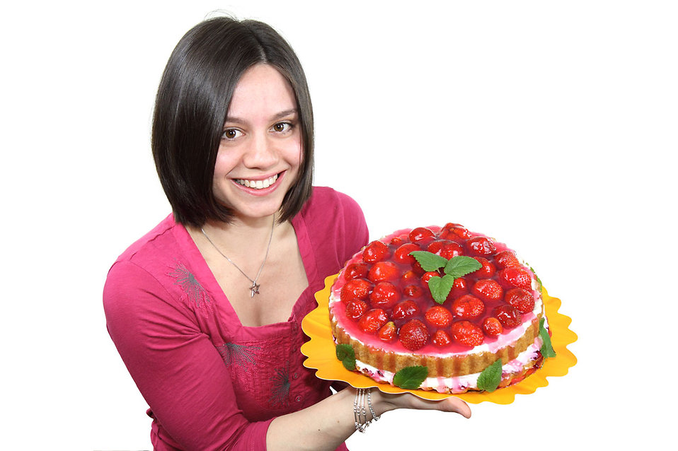 A beautiful woman holding a strawberry cake isolated on a white background.