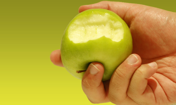A hand holding a bitten green apple : Free Stock Photo