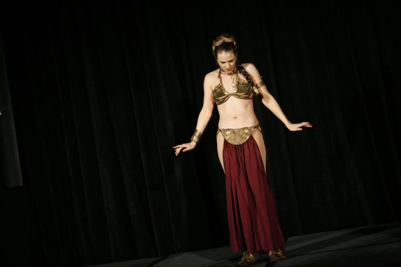 A beautiful girl in a Princess Leia slave girl costume teaches belly dancing : Free Stock Photo