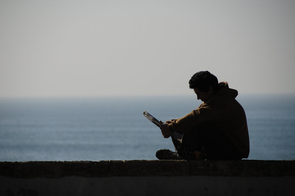 Silhouette of a man reading by the ocean : Free Stock Photo