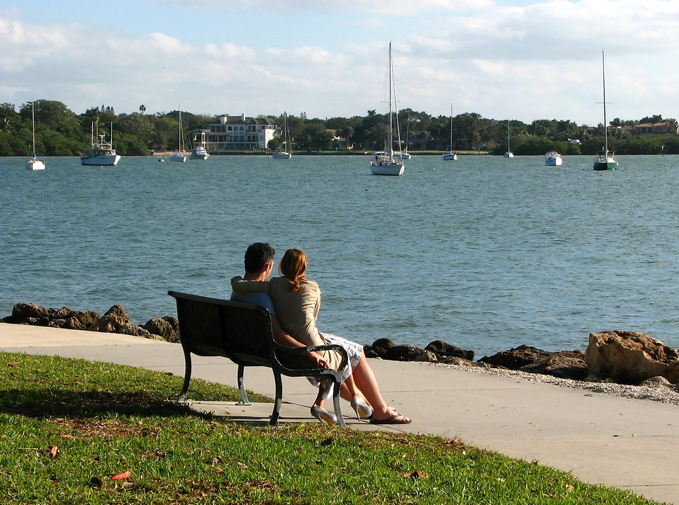 A couple sitting on a bench overlooking the ocean : Free Stock Photo