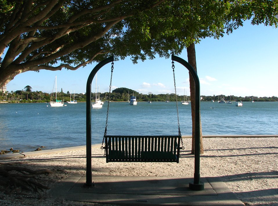 A swinging chair in a park overlooking the ocean : Free Stock Photo