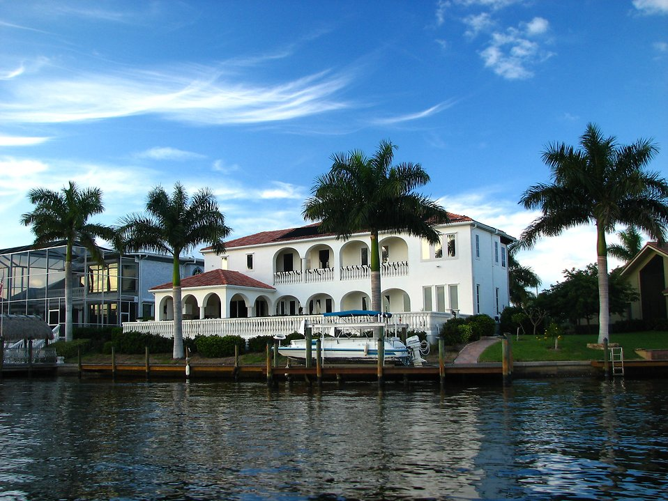 A fancy house along the water with palm trees.