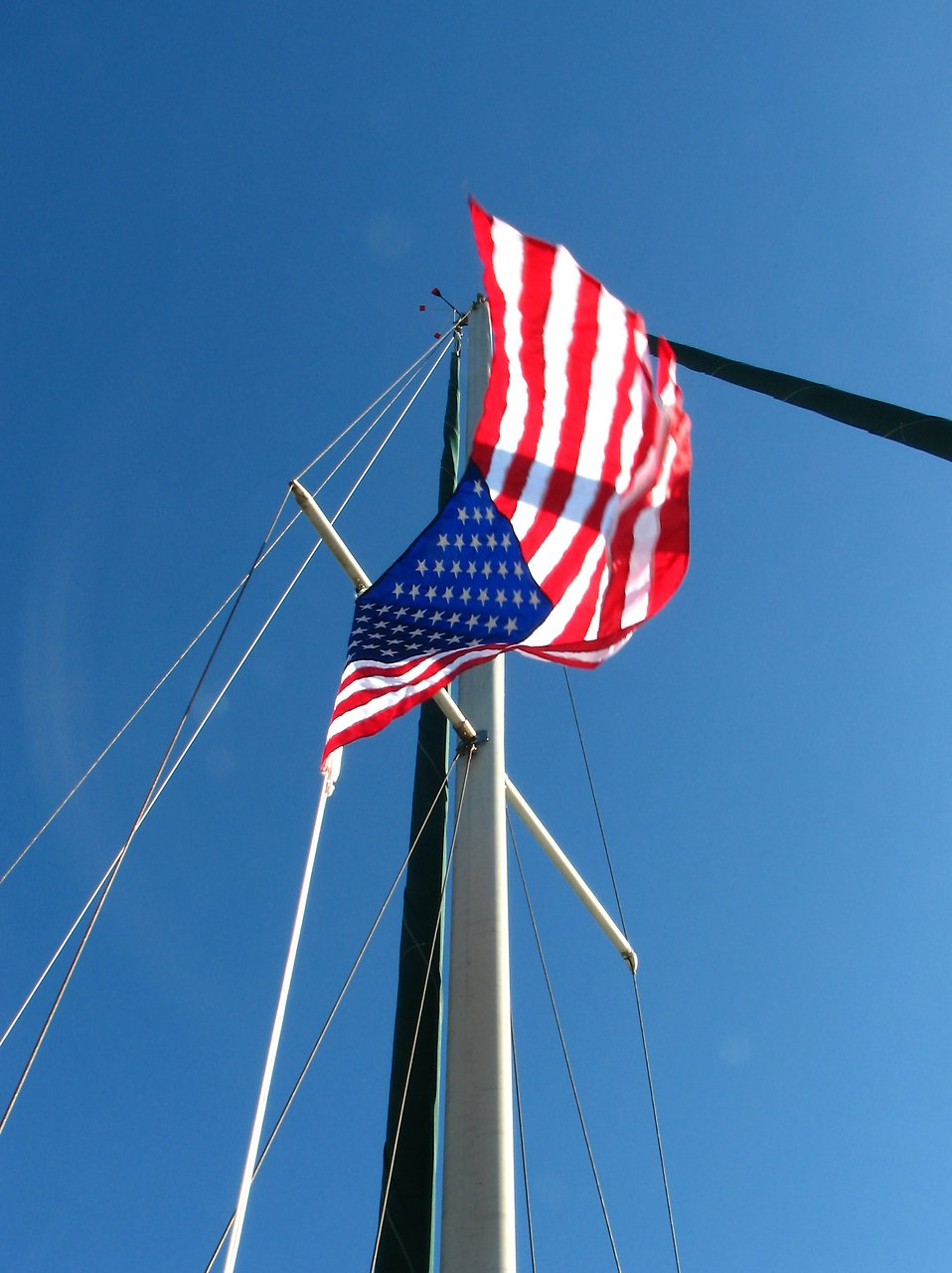 A flag flying on the mast of a sailboat : Free Stock Photo