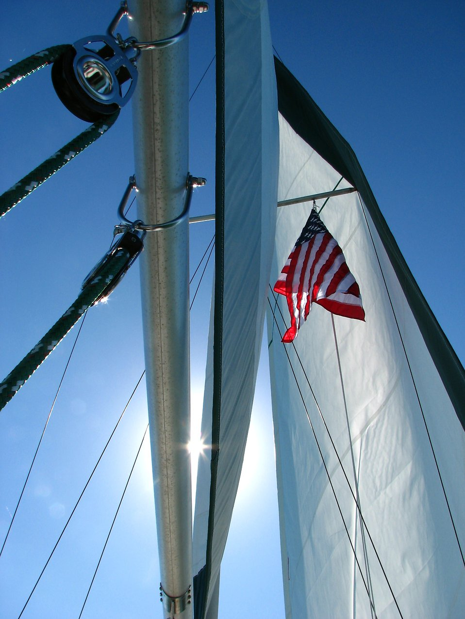 An American flag and the sail of a sailboat : Free Stock Photo