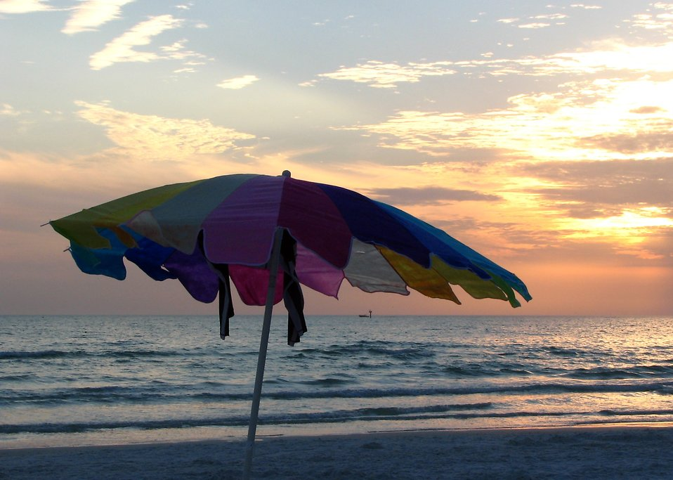 A beach umbrella in front of a sunset : Free Stock Photo