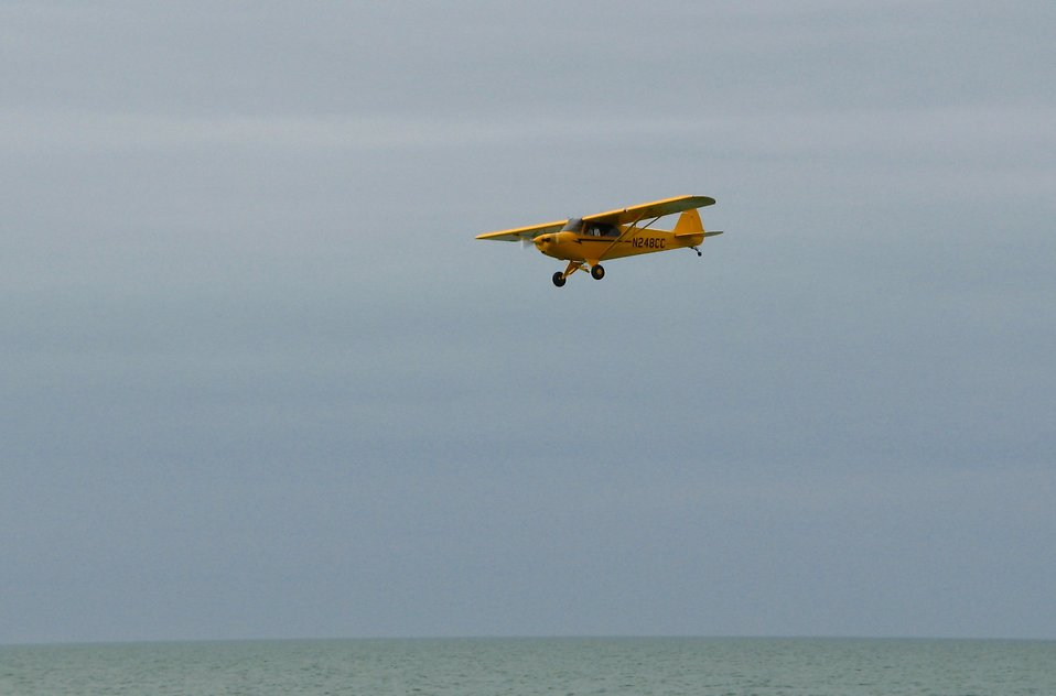 A yellow airplane flying over the ocean : Free Stock Photo