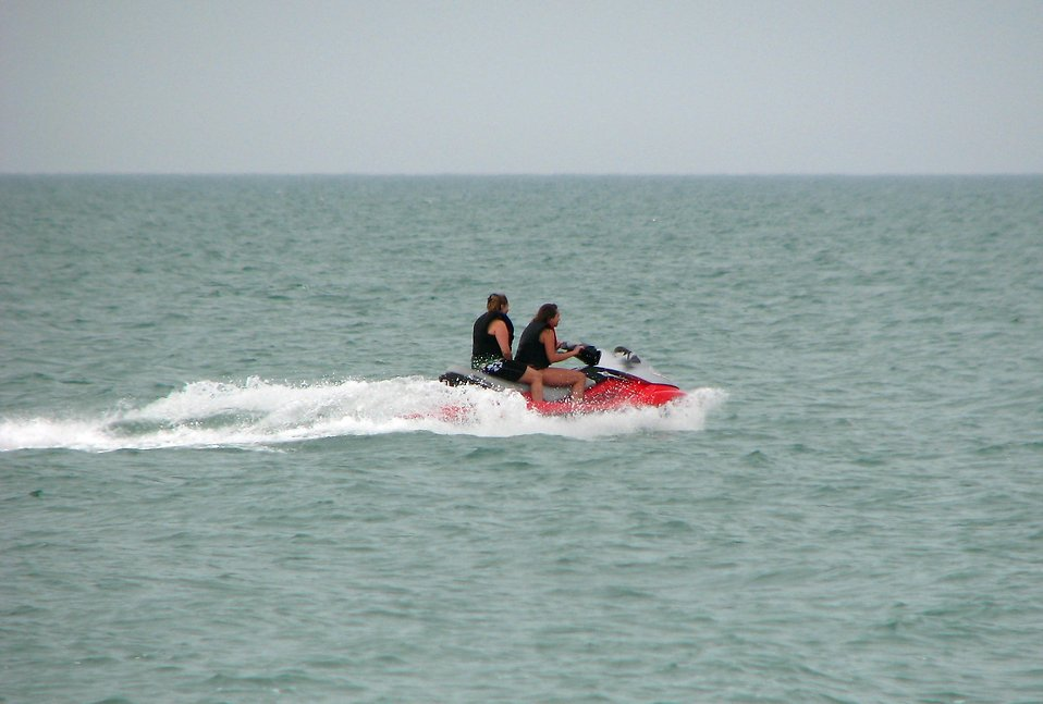 People riding a waverunner on the ocean : Free Stock Photo