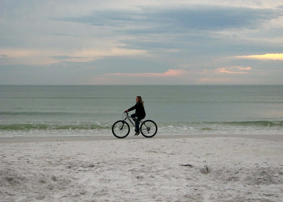 A woman riding a bike on the beach : Free Stock Photo