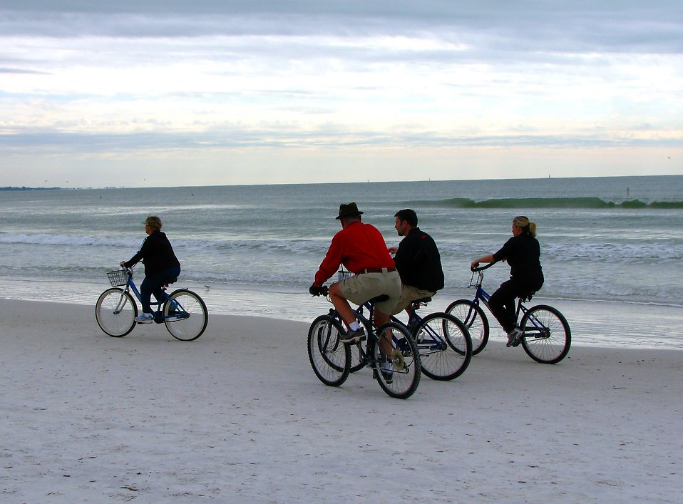 People riding bikes on the beach : Free Stock Photo