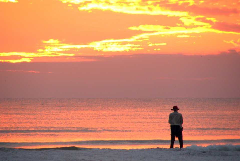 A person watching the sunset on the beach : Free Stock Photo
