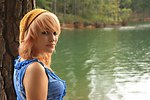 Free Stock Photo: A beautiful young woman posing against a tree by a lake
