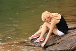 Free Stock Photo: A beautiful young woman posing on a rock by a lake