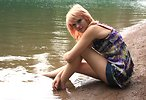 Free Stock Photo: A beautiful young woman posing on the shore of a lake