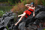 Free Stock Photo: A beautiful young woman posing in a red dress on rocks by a lake