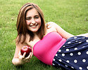 Free Stock Photo: A beautiful young girl holding an apple in the grass