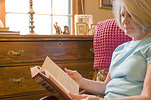 Free Stock Photo: A woman reading a book in her home