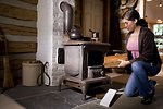 Free Stock Photo: A woman placing wood into a stove