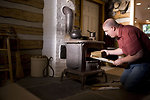 Free Stock Photo: A man placing wood into a stove