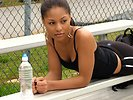 Free Stock Photo: A beautiful teen African American girl resting on bleachers with a bottle of water