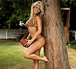 Free Stock Photo: A beautiful blond posing against a tree with a football