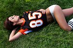 Free Stock Photo: A beautiful girl in a football jersey lying in the grass