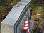 Free Stock Photo: US flag leaning against a tombstone