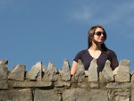 Free Stock Photo: A beautiful girl standing behind a stone wall