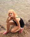 Free Stock Photo: A beautiful young woman posing on rocks by a lake