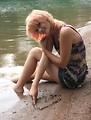Free Stock Photo: A beautiful young woman drawing a heart in the sand by a lake