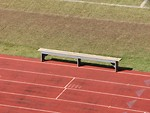 Free Stock Photo: An empty bench on a track field