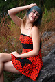Free Stock Photo: A beautiful young woman posing in a red dress on rocks