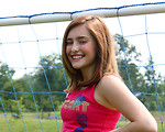 Free Stock Photo: A cute young girl posing by a soccer goal