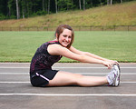 Free Stock Photo: A cute young girl doing stretches on a track field
