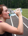 Free Stock Photo: A cute young girl drinking water on a track field