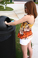 Free Stock Photo: A young girl throwing away trash in a trash can